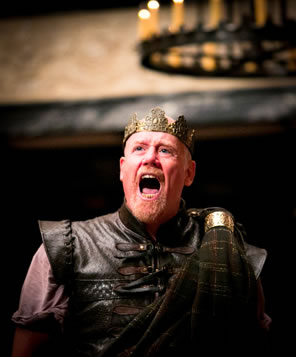 Macbeth in leather armor and crown on his head, mouth open in a shout with theater chandelier in the background