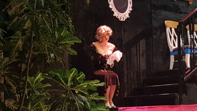 Ophelia in brown dress just below her knees works on needlepoint on a stage with red carpet, wood stairs, and green plants.