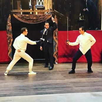 Hamlet in white with black glove holding foil faces off with Laertes in white fencing shirt and black pants, with Horatio in a suit and tie in the middle as referee