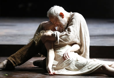Lear in linen shit and brown pants cries with his forehead resting against the chin of Cordelia who lies dead in his arms, her body still dressed in the white slip