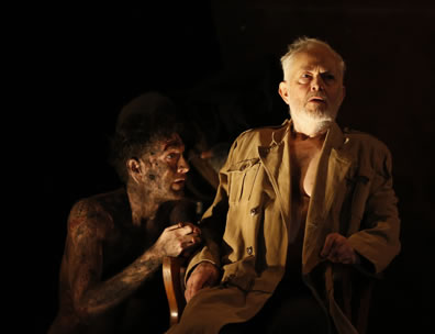 A begrimed Edgar looks up at Lear, shirtless but in trenchcoat sitting in a chair against a deep dark background