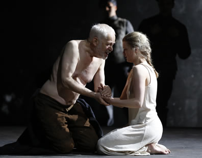 A shirtless Lear in brown pants, and Cordelia in white ankle-length slip kneel on the ground and clasp hands