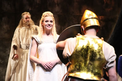 Simonides in background in cream robe and curly beard, Thaisa in white gown and blond tressels, her hands folded at her waist and smiling as she looks on the shield the knight, his back to us, is holding up, he wearing a greenish gold breastplat and simple, gold, conical helmet.