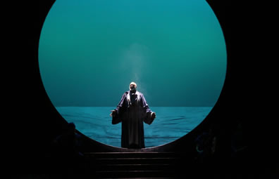 Gower in robes stands with hands outstretched in the middle of a giant circle with a sea behind him and steps leading down to the stage