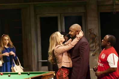 Adriana hugs a bemuse Lenny Henry in a pool hall as Dromio and Luciana look on.