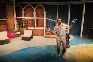 Benedick in tan beach shirt and swim trunks with sunglasses in one hand and blue bottle of lotion in the other with a folded up beachchair hanging over his shoulder.