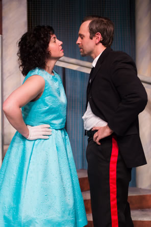Beatrice in blue party dress and white gloves, Benedick in black uniform with red piping on the pants, both facing each other nose to nose with hands on hips.