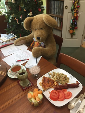 A big brown teddy bear sits at a dining room table, recipes spread in front of her, and a dish of food at the seat next to hers