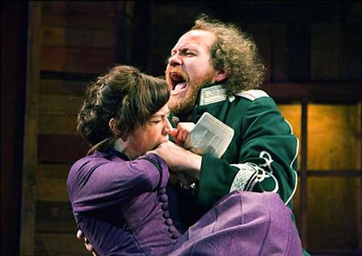 Kate in a purple dress, bites Petruchio's hand