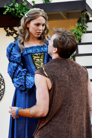 Rosalind in blue dress with gold panel front and ruched bodice and sleeves stands looking down at a kneeling Orlando wearing a brown-patterned vest with now shirt.