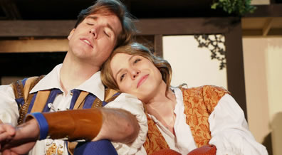 Orlando in blue and tan embroidered vest over white shirt, his leath-forearm-banned arm resting on his knee, Rosalind in floral gold vest on white shirt, the knees of her orange britches visible, and her head leaning on Orlando's shoulder.
