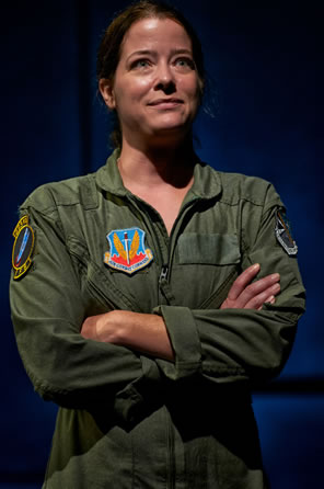The Pilot in olive green flight suit, with a unit patch on the right breast. stands with arms crossed, looking confidently to the horizon