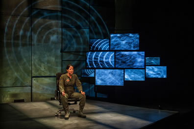 The Pilot in olive green flightsuit and boots sits in a chair with rollers, hands on knees, one with thumb up as if she's controlling a joystick, a bank of video screens behind her to the lest with images of a radar tracker over a dessert landscape, and a larger version of the same image projected on the wall behind her.