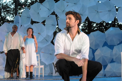 Ferdinand squatting at the front center of the picture in white shirt with gold collar and black pants, in the back ground Prospero in white shirt, ragged black pants ending at his knees, and Miranda in simple white dress with blue shading and black boots, behind them a chair, and the umbrellas of the stage wall, with real trees beyond those
