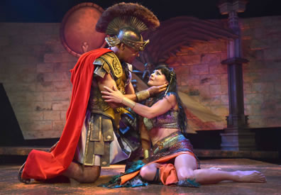 Antony in classic Roman legion uniform, skirt, leather armo, crest helmet and red ape on his knees stroking Cleopatra's neck as she holds  his arm, she sitting on the floor in a multi-colored sheen dress, halter, and bare midriff