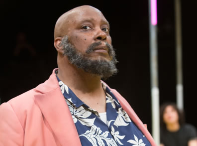 Thomas as Falstaff wearing pink jacket over flowered blue shirt, a full beard and bald head