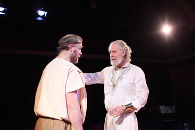 Timon in white nobleman's gown, gold medallion and wristbands talks gently with Flavius in simple shirt and pants and a headband
