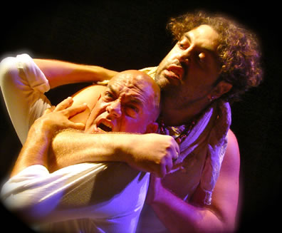 Curly haired, bearded Aufidius with bare arms has bald Coriolanus wearing a white T-shirt in a headlock