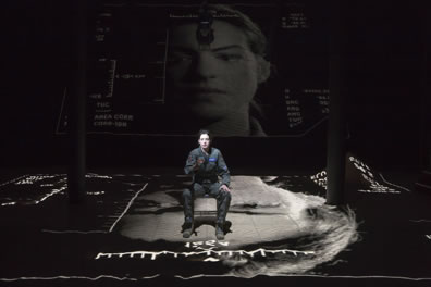 Hathaway in a flight suit sits on a chair in the middle of a gray-toned landscape with various coordinates on the edges, and a larger portrait of her projected on a screen in the background.