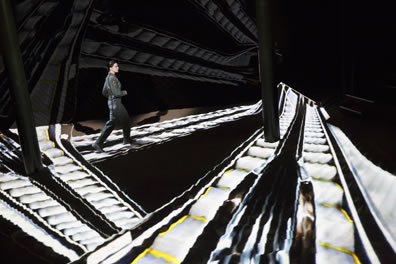 Hathaway, wearing a flightsuit, walking on an escalator, one of three criss-crossing the floor as projected on the sand