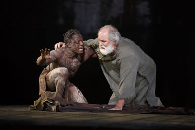 Edgar in only a loin cloth around his waist and hand up, kneels with Lear, in simple burlap-like rope, one hand on the groound,the other around Edgar's shoulder