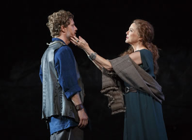 Goneril on the right strokes Edmund's beard with her fingertips; she is wearing a blue dress with a gray scarf draped over her arms and around her waist, he is in blue shirt, gray pants and gray leather vest.