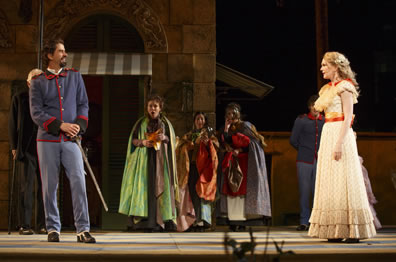 Benedick in pale blue army officers uniform with hands on hilt stands to one side across from Beatrice in yellow layered dress, while the other characters stand in the background in cloaks.