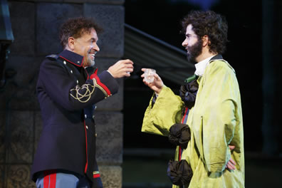 Don Pedro in dark blue army officers coat with red braids and light blue uniform pants with red piping holds a glass up to Benedick wearing a lime green clown costum with big puffy black buttons