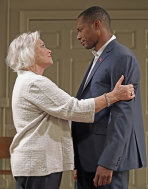 Volumnia, short gray hair, white jacket blouse, gray pants, grasps Martius's arms as she looks up at him and he, in gray suit, down sheepishly at her.