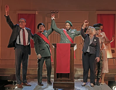 Menenius waves with right hand, wearing dark gray suit, white shirt, muted red tie, and black suspenders; Comininius in army service uniform and beret with a red sash holds up Coriolanus's right arm; Coriolanus behind podium in army service uniform, green beret, and red sash; Volumnia, holding up her son's left hand, in breay jacket, blouse, and pants; Young Martius in camoflauge pants and fatigue t-shirt waves to side; Virgilia behind her in simple tan blouse and skirt with white long coat over her shoulders, waving.