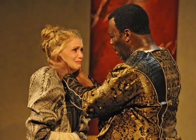 Othello has his hands around Desdemona's neck as she cries looking up at him. Both are dressed in ornate gold and black Renaissance outfits