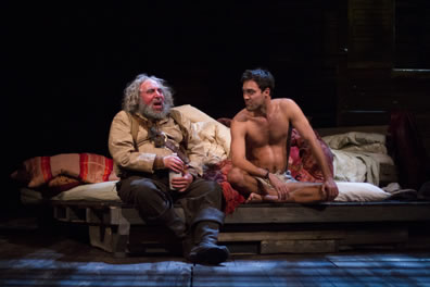 Falstaff in gray beard, cream shirt and tan vest with brown pants and black boots holdig a white bottle sits on the edg of a rumpled bed next to Hal, naked except for his briefs