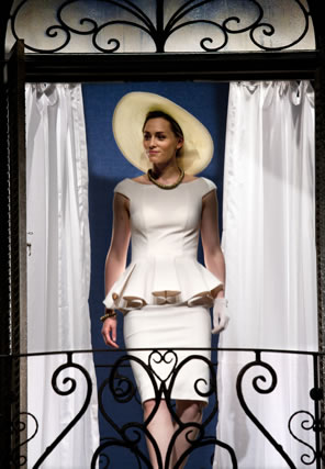 Siliva in tight white knee-length dress, a blouse that hugs the shoulder and bosom and spreads out in pleats at the waste, and a white wide-brimmed hat walks through the curtains of a wrought-iron balcony.