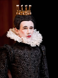 Man wearing woman's makeup in Elizabethan black dress with large ruff colar, gold crown with upright prongs on tight black wig