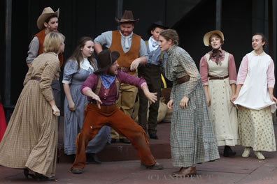 Several people in old West clothing watch two women face off as Pompey in the middle, wearing purple shirt and red pants, stands between the combatants backing them away from each other