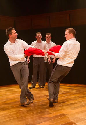Two boys pulling on a red fabric circle each other as two other boys in the background watch, all in white shirts and tan trousers.