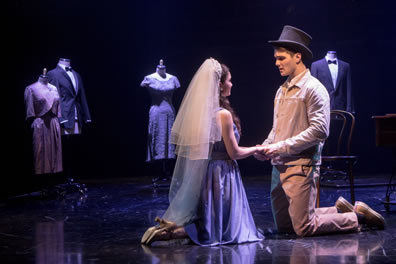 Maria and Tony kneel on the stage and holding hands,  she in simple dress and wearing a wedding veil, he in brown work shirt and pants wearing a black tophat. In the background are maniquins with formal suits and nice dresses