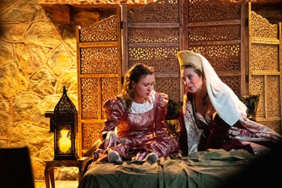 Production photo of Juliet and Lady Capulet on her bed. Photo by Kenneth Garrett