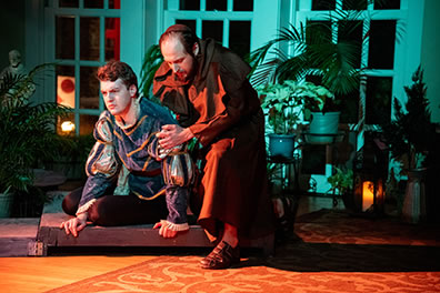 Production photo of Romeo on the ground and Friar Laurence comforitng him. Photo by Kenneth Garrett