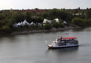 Photo of tents by the river and river boat