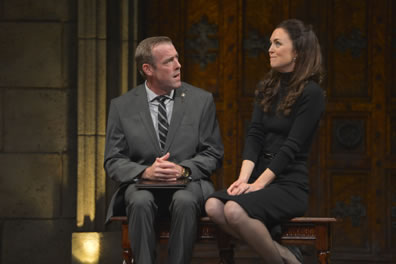 Sitting on a bench with a stone wall and large wooden door in the background, Prime Minister Evans in gray suit and shirt, black and white striped tie, hands folded on a black notebook, has his head turned as he talks to Kate sitting sideways, legs crossed demurely, hands pressing into her lap, a plain blck dress and a far-away look of contemplation.