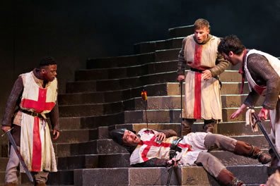 Three soldiers wearing Saint George smocks over chain-mail armor stand around another soldier lying on the stone steps with an arrow sticking into his shoulder, blood on the smock, his hand gripping at his breast, a sword in his other hand.