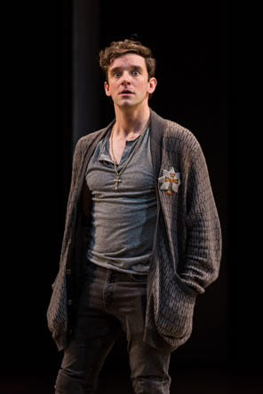 Hamlet in gray t-shirt and jeans and sweater with a cross emblem on the lapel and a cross necklace around his neck, his hands shoved in the sweater's pockets, and his eyes so wide the white surrounds the pupils.