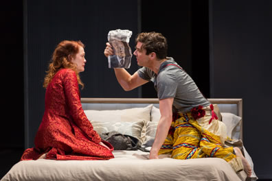 Hamlet in gray t-shirt and jester's pants holds up a small poster of his father to Gertrude, wearing a red robe, both kneeling on the bed.