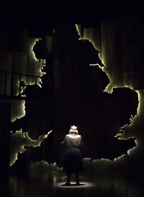 Henry, back to us, stands in a spotlight looking up at a giant silhouette map of England outlined in white light.