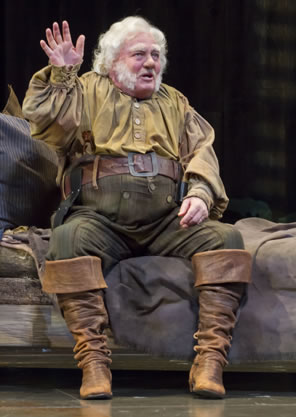 Falstaff in dirty yellow shirt, striped green pants and brown boots waves his right hand as he sits on a bed.