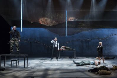 With bodies lying on the stage, the Weird Sisters talk on cell phones, one in combat gear standing on a table to the left, one in white shirt, black pants  and shoulder holster standing at the back center, the woman in business suit and skirt standing to the right.