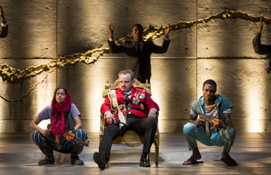 Macbeth slouches in a low-back thrown, wearing a red uniform jacket with medals, fringed shoulder braids and sash. On both sides, two young soldiers squat, both holding AK-47 rifles. the boy in aqua pants, striped shirt and sweater tied around his shoulders, the girl in striped blued pants, purple tea, and red hajib. In the background, Fleance in a suit has his arms raised.