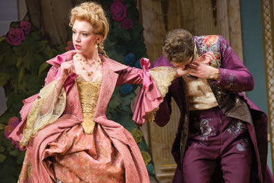 Lucille in a pink cloak over a pink floral-patterend hoop skirt with yellow lace corset and drooping lace sleeves, her blond hair tied up in curls, Dorante in purple pants and long coat with psychodelic splotches on the pants and coat trim, and a yellow shirt. He is kissing her left hand, she's looking the other way.