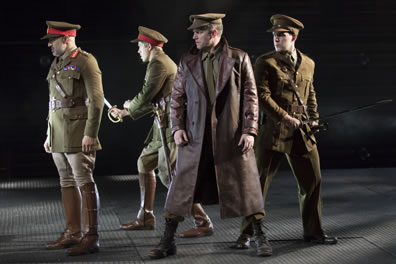 Othello and others stand in military uniforms with olive green service jackets, khaki jodhurs, brown boots, billed caps with red bands around them; two of the soldiers have their swords drawn; Iago stands in front, legs wide apart, in shin-length brown leather trench coat.